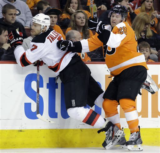 Philadelphia Flyers' Claude Giroux, right, checks New Jersey Devils' Henrik Tallinder, of Sweden, into the boards during the second period of an NHL hockey game, Thursday, April 18, 2013, in Philadelphia. (AP Photo/Matt Slocum)