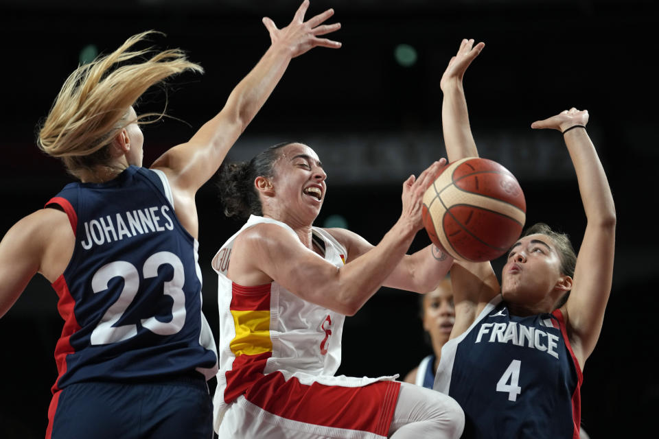 Spain's Silvia Dominguez, center, drives to the basket between France's Marine Johannes (23) and Marine Fauthoux (4) during a women's basketball quarterfinal round game at the 2020 Summer Olympics, Wednesday, Aug. 4, 2021, in Saitama, Japan. (AP Photo/Eric Gay)