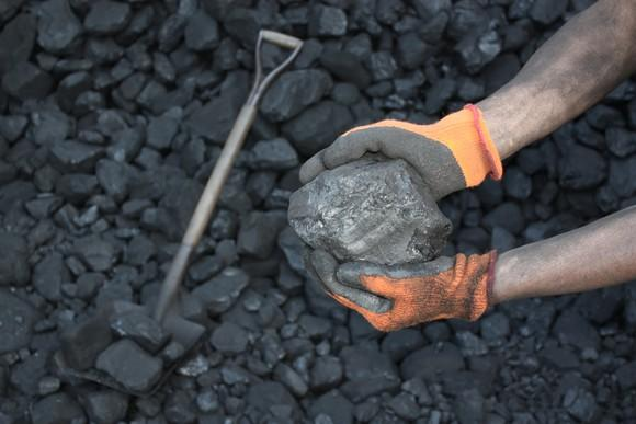 A man holding coal in his orange-gloved hands.