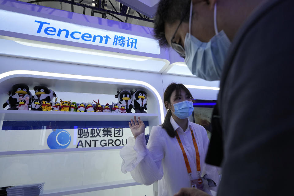 A worker attends to a visitor at the Tencent booth during China International Fair for Trade in Services (CIFTIS) in Beijing, China on Monday, Sept. 6, 2021. Tencent Holdings Ltd., best known abroad for its WeChat messaging service, has a sprawling business empire that includes games, music and video. (AP Photo/Ng Han Guan)