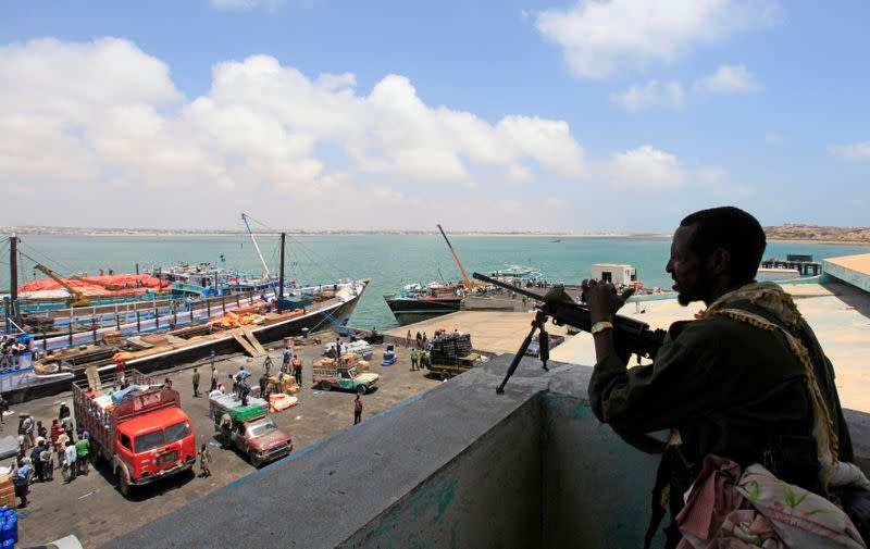 FILE PHOTO: A soldier from Somalia's Ras-Kamboni paramilitary group stands guard as he monitors activities at the sea port in lower juba regions in Kismayu
