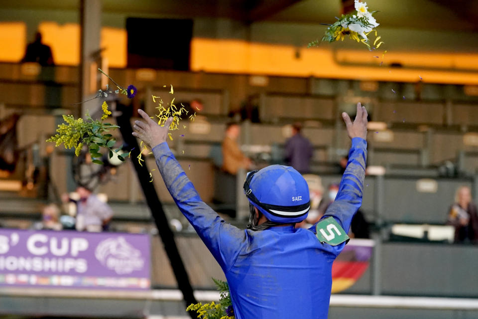 Luis Saez tosses flowers in the air after guiding Essential Quality to win the Breeders' Cup Juvenile horse race at Keeneland Race Course, Friday, Nov. 6, 2020, in Lexington, Ky. (AP Photo/Darron Cummings)