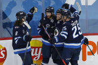 Winnipeg Jets' Sami Niku (8), Kyle Connor (81), Nikolaj Ehlers (27) and Paul Stastny (25) celebrate Connors' goal against Montreal Canadiens goaltender Carey Price during second-period NHL hockey game action in Winnipeg, Manitoba, Thursday, Feb. 25, 2021. (John Woods/The Canadian Press via AP)