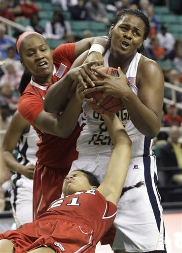 Georgia Tech's Sasha Goodlett, right, and North Carolina State players Bonae Holston, left, and Erica Donovan, bottom, wrestle for control of a rebound during the first half of an NCAA Atlantic Coast Conference women's tournament basketball game in Greensboro, N.C., Saturday, March 3, 2012. (AP Photo/Chuck Burton)