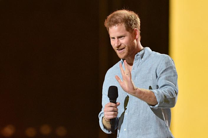 """Co-Chair Britain's Prince Harry, Duke of Sussex, waves as he speaks onstage to speak during the taping of the """"Vax Live"""" fundraising concert at SoFi Stadium in Inglewood, California, on May 2, 2021. - The fundraising concert """"Vax Live: The Concert To Reunite The World"""", put on by international advocacy organization Global Citizen, is pushing businesses to """"donate dollars for doses,"""" and for G7 governments to share excess vaccines. The concert will be pre-taped on May 2 in Los Angeles, and will stream on YouTube along with American television networks ABC and CBS on May 8. (Photo by VALERIE MACON / AFP) (Photo by VALERIE MACON/AFP via Getty Images) ORG XMIT: 0 ORIG FILE ID: AFP_9986GT.jpg"""