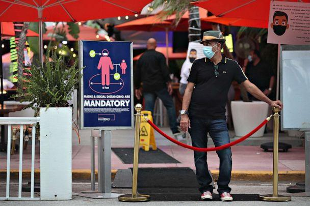 PHOTO: Juan Carlos, a host at Ocean 10 restaurant, stands at the entrance of the restaurant to turn customers away as a curfew from 8pm to 6am is put in place on July 18, 2020, in Miami Beach, Fla. (Joe Raedle/Getty Images)