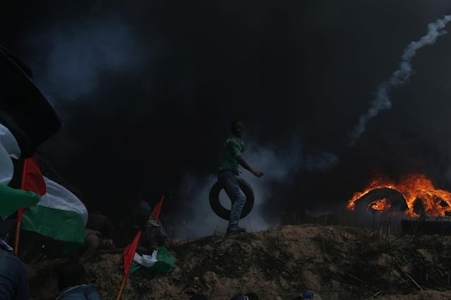 <p>A Palestinian demonstrator carries a tire as others take cover from Israeli fire and tear gas during a protest against the U.S. Embassy's move to Jerusalem and ahead of the 70th anniversary of Nakba, at the Israel-Gaza border in the southern Gaza Strip on May 14, 2018. (Photo: Ibraheem Abu Mustafa/Reuters) </p>