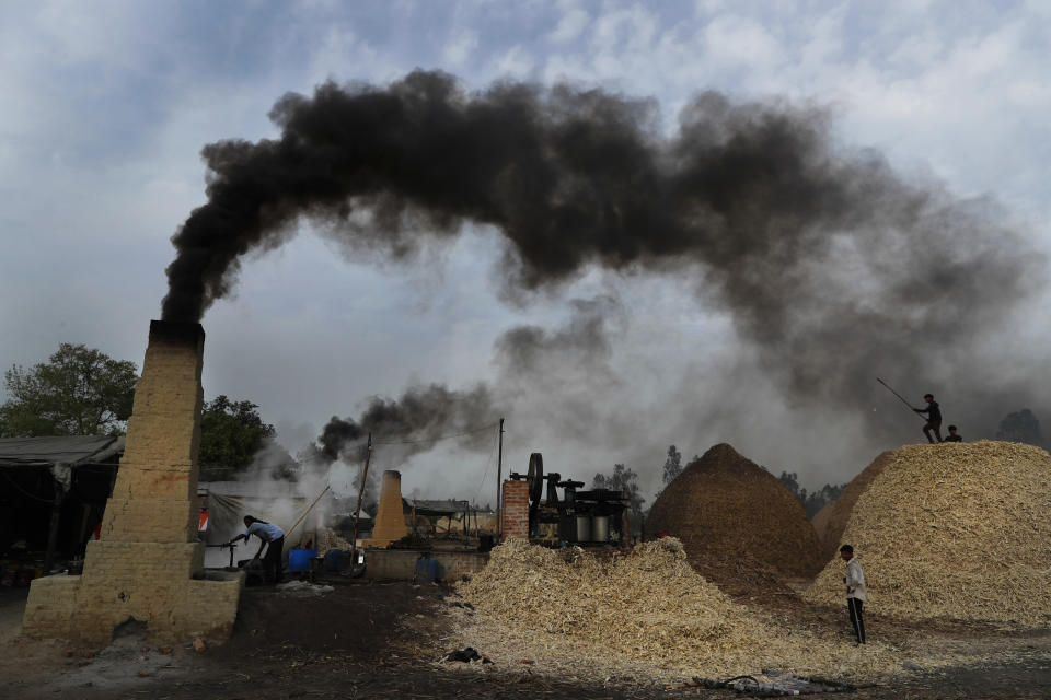 Smoke rises from chimneys as workers prepare jaggery on the outskirts of Bareilly, India, Tuesday, March 23, 2021. Jaggery is a traditional unrefined sugar consumed in many parts of Asia, made from molasses of sugarcane and date palm sap. (AP Photo/Rajesh Kumar Singh)