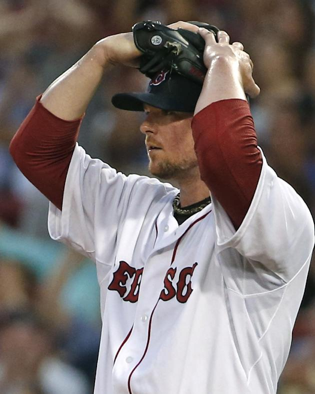 Boston Red Sox starting pitcher Jon Lester reacts as center fielder Brock Holt makes a difficult catch of a fly out by Minnesota Twins' Brian Dozier which was momentarily lost in the outfield lights during the third inning of a baseball game at Fenway Park in Boston, Tuesday, June 17, 2014. (AP Photo/Elise Amendola)