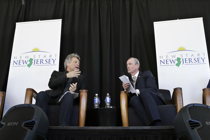 FILE – In this Nov. 10, 2014, file photo, Philip Murphy, right, former U.S. ambassador to Germany in President Barack Obama's administration, listens as rock musician Jon Bon Jovi, left, speaks during an event to launch New Start New Jersey, a group seeking to influence policy in support of New Jersey's middle class, in Newark, N.J. Jim Johnson, a former treasury official in President Bill Clinton's administration, requested Thursday, March 30, 2017, that the Election Law Enforcement Commission investigate Murphy, a Democratic candidate for New Jersey governor and former Goldman Sachs executive. Johnson's campaign alleges two groups Murphy set up before officially entering the governor's race, New Start New Jersey and New Way for New Jersey, constituted exploratory committees. (AP Photo/Mel Evans, File)