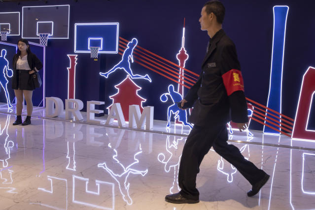 "In this Friday, Oct. 11, 2019, photo, a security guard walks past neon light decor depicting basketball players and silhouette of iconic Chinese buildings in Beijing. When Houston Rockets' general manager Daryl Morey tweeted last week in support of anti-government protests in Hong Kong, everything changed for NBA fans in China. A new chant flooded Chinese sports forums: ""I can live without basketball, but I can't live without my motherland.""(AP Photo/Ng Han Guan)"