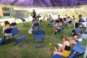Andrea Gurney, Westmont professor of psychology, teaches masked and socially distant students under a tent on Winter Lawn.