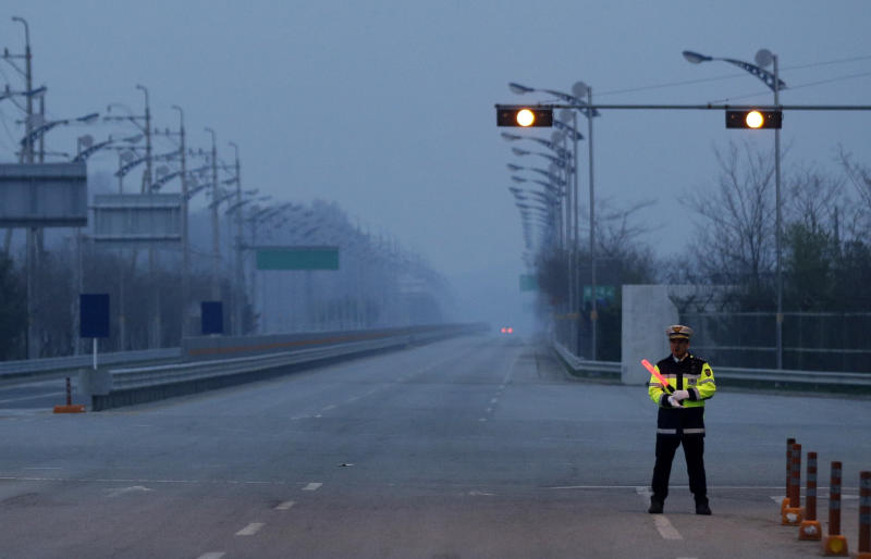 A South Korean police officer stands on an empty road at the customs, immigration and quarantine office near the border village of Panmunjom, that has separated the two Koreas since the Korean War, in Paju, north of Seoul, South Korea, Friday, May 3, 2013. The last South Koreans stationed at a jointly run factory park in North Korea pulled out Friday, dealing a major blow to the rivals' only remaining symbol of rapprochement and rendering them with virtually no official communication channel. (AP Photo/Lee Jin-man)