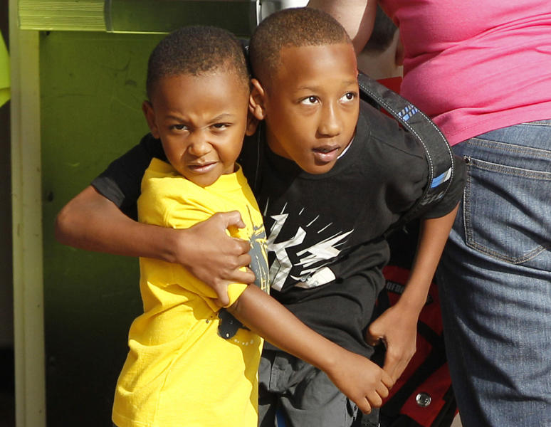 Cam'ron Richardson, right, hugs his brother Anthony Richardson as he heads in for the first day of school at Plaza Towers Elementary School in their temporary location at Central Jr. High School in Moore, Okla., Friday, Aug. 16, 2013. The Briarwood and Plaza Towers elementary schools were destroyed when an EF5 twister hit Moore on May 20. Cam'ron was trapped under the rubble of the tornado that killed two dozen people. (AP Photo/Sue Ogrocki)