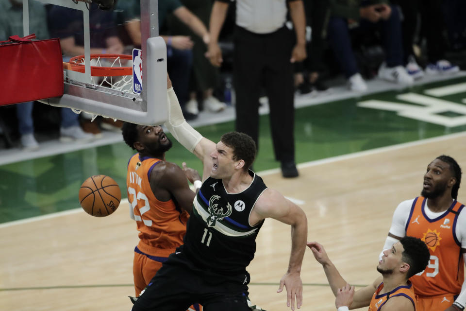 Milwaukee Bucks center Brook Lopez (11) slam dunks over Phoenix Suns center Deandre Ayton (22), guard Devin Booker and forward Jae Crowder, right, during the second half of Game 6 of basketball's NBA Finals Tuesday, July 20, 2021, in Milwaukee. (AP Photo/Aaron Gash)