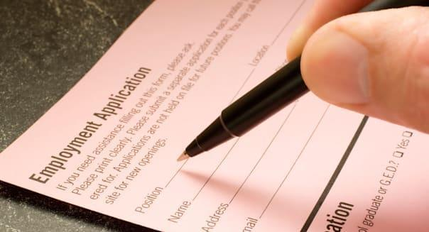 Man s hand filling out an employment application with a ballpoint pen