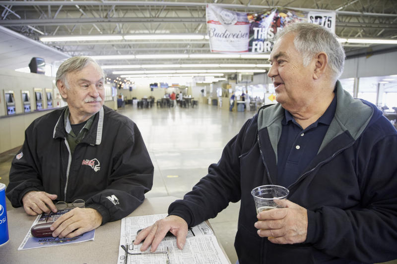 """Ron Tenski and Jerry Moritz, right, who had arrived to Fonner Park in Grand Island, Neb., for the horse races, Saturday, March 14, 2020, prepares to leave after the races were called off due to dangerous track conditions following snowfall. Fonner was one of the few sporting venues in the country open to fans Saturday, and Moritz wasn't going to let concerns over the new coronavirus stop him from going to the track. """"If we had a dozen people in the hospital here and two or three died, then I would probably back off,"""" he said. """"I feel like some people probably got it and don't even know it and are already over it."""" (AP Photo/Nati Harnik)"""