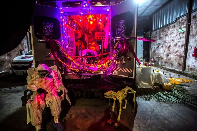 Paramedics specialized in the transfer of patients with Covid-19 symptoms set up a stark installation to commemorate the Day of the Dead in Merida City, Yucatan state