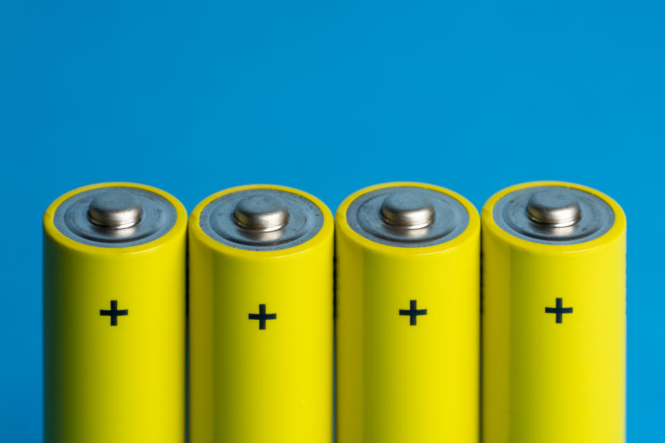Elevated view of four yellow batteries on a blue colored background