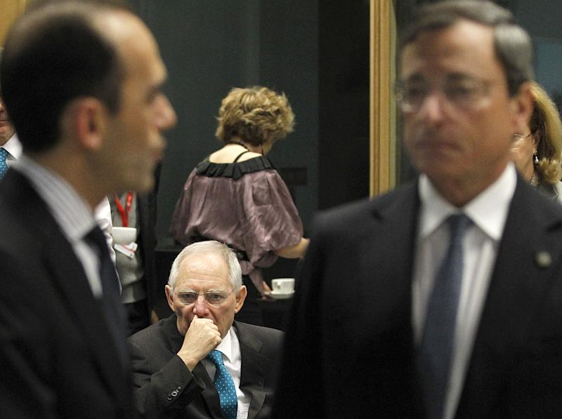 German Finance Minister Wolfgang Schauble, center, sits as Cyprus Finance Minister Harris Georgiades, left, talks with European Central Bank President Mario Draghi, right, before an informal meeting of the Economic and Financial Affairs Council (ECOFIN) in Dublin, Ireland, Friday, April 12, 2013. (AP Photo/Peter Morrison)