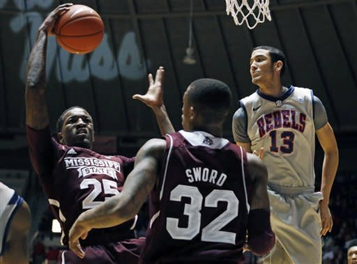 Mississippi State forward Roquez Johnson (25) pulls down a rebound in front of guard Craig Sword (32) and Mississippi forward Anthony Perez (13) in the first half of their NCAA college basketball game in Oxford, Miss., Wednesday, Feb. 6, 2013. (AP Photo/Rogelio V. Solis)