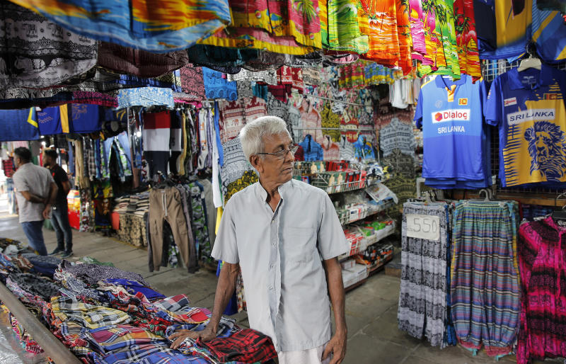 """In this July 24, 2019, photo, Sri Lankan trader Ranepura Hewage Jayasena, 76, waits for customers at shop selling mementos in Colombo, Sri Lanka. Shocks from deadly suicide bombings on Easter Day in Sri Lanka are still reverberating throughout its economy in the worst crisis since the South Asian island nation's civil war ended in 2009. """"Almost 100% of my business is gone. There are days without a single sale,"""" said Jayasena, looking grief-stricken as he went through the previous days accounts. """"We had a war that raged for years, but we had good business. Bombs exploded in Colombo city itself, but that did not affect our business,"""" he said. """"This is the worst period I have seen in my life."""" (AP Photo/Eranga Jayawardena)"""