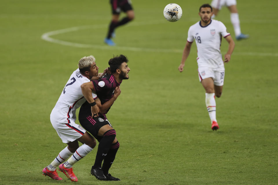 Mexico's Alexis Vega, center, is challenged by United States' Julian Araujo during a Concacaf Men's Olympic Qualifying championship soccer match in Guadalajara, Mexico, Wednesday, March 24, 2021. (AP Photo/Fernando Llano)
