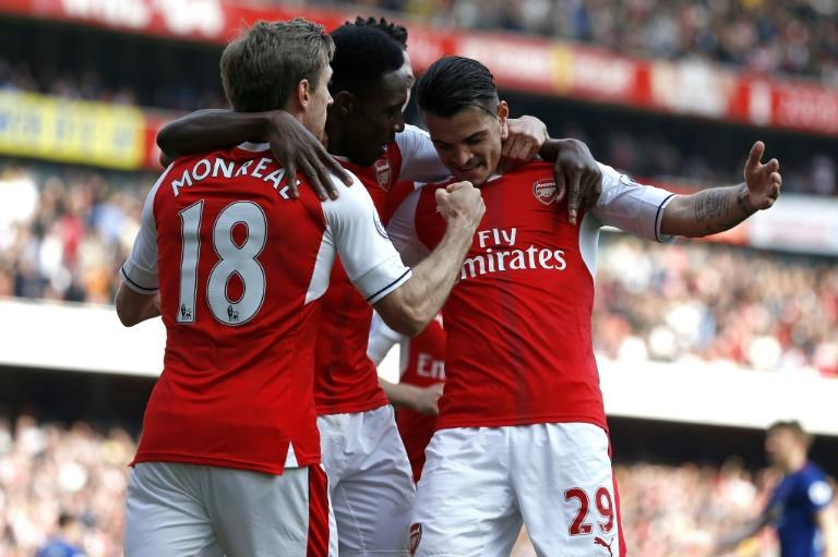 Arsenal players celebrate after scoring the opening goal of the English Premier League football match against Manchester United in London on May 7, 2017