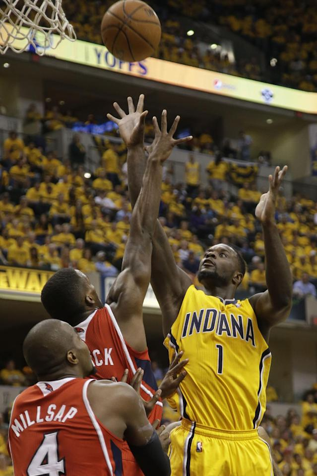 Indiana Pacers guard Lance Stephenson (1) shoots over Atlanta Hawks defenders Shelvin Mack and Paul Millsap (4) in the second half during Game 7 of a first-round NBA basketball playoff series in Indianapolis, Saturday, May 3, 2014. The Pacers won 92-80. (AP Photo/AJ Mast)