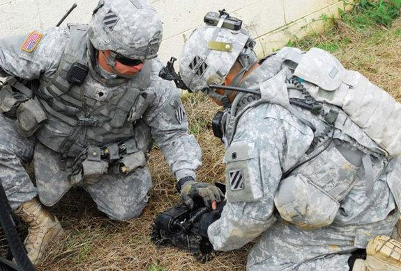 Two Soldiers prepare a robot for a mission Wednesday as part of the experiment at Fort Benning, Ga.