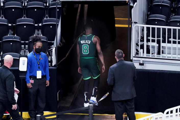 Boston Celtics guard Kemba Walker (8) heads to the locker room after an apparent injury early during the first quarter of the team's NBA basketball game against the Miami Heat, Tuesday, May 11, 2021, in Boston. (AP Photo/Charles Krupa)