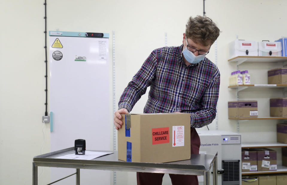FILE - In this Saturday Jan. 2, 2021 file photo, Assistant Technical Officer Lukasz Najdrowski unpacks doses of the COVID-19 vaccine developed by Oxford University and U.K.-based drugmaker AstraZeneca as they arrive at the Princess Royal Hospital in Haywards Heath, England. Britain races to vaccinate more than 15 million people by mid-February, and in an effort to ensure vaccines get to the right places at the right times, along with the syringes, alcohol swabs and protective equipment needed to administer them, the government has called in the army. (Gareth Fuller/Pool via AP, File)