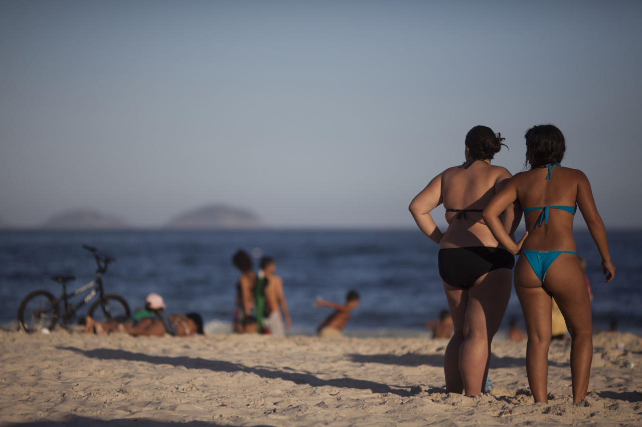 In this photo taken Jan. 23, 2012, women stand at Copacabana beach in Rio de Janeiro, Brazil. A growing number of bikini manufacturers have woken up to Brazil's thickening waistline and are reaching out to the ever-expanding ranks of heavy women with new plus-size lines. (AP Photo/Felipe Dana)