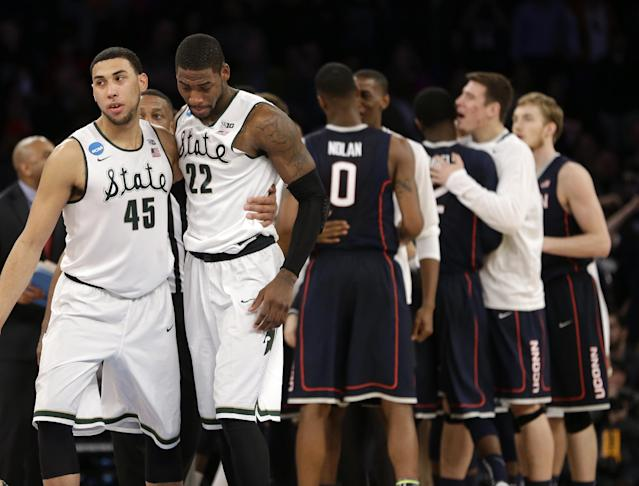 Michigan State's Denzel Valentine, left, and Branden Dawson go by celebrating Connecticut players after loosing against Connecticut 60-54 in a regional final at the NCAA college basketball tournament, Sunday, March 30, 2014, in New York. (AP Photo/Seth Wenig)