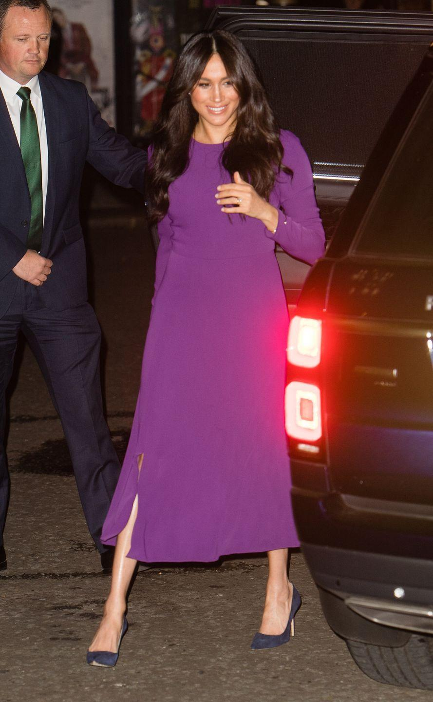 <p>The Duchess of Sussex arrived at the One Young World Summit in a purple Aritzia dress, which she paired with her blue Manolo Blahnik pumps.</p>