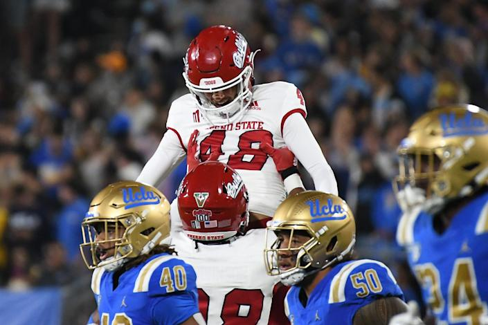 Fresno State place kicker Abraham Montano (48) celebrates with defensive tackle Dario Pizzuti (98) after a field goal against the UCLA Bruins in the third quarter at Rose Bowl.