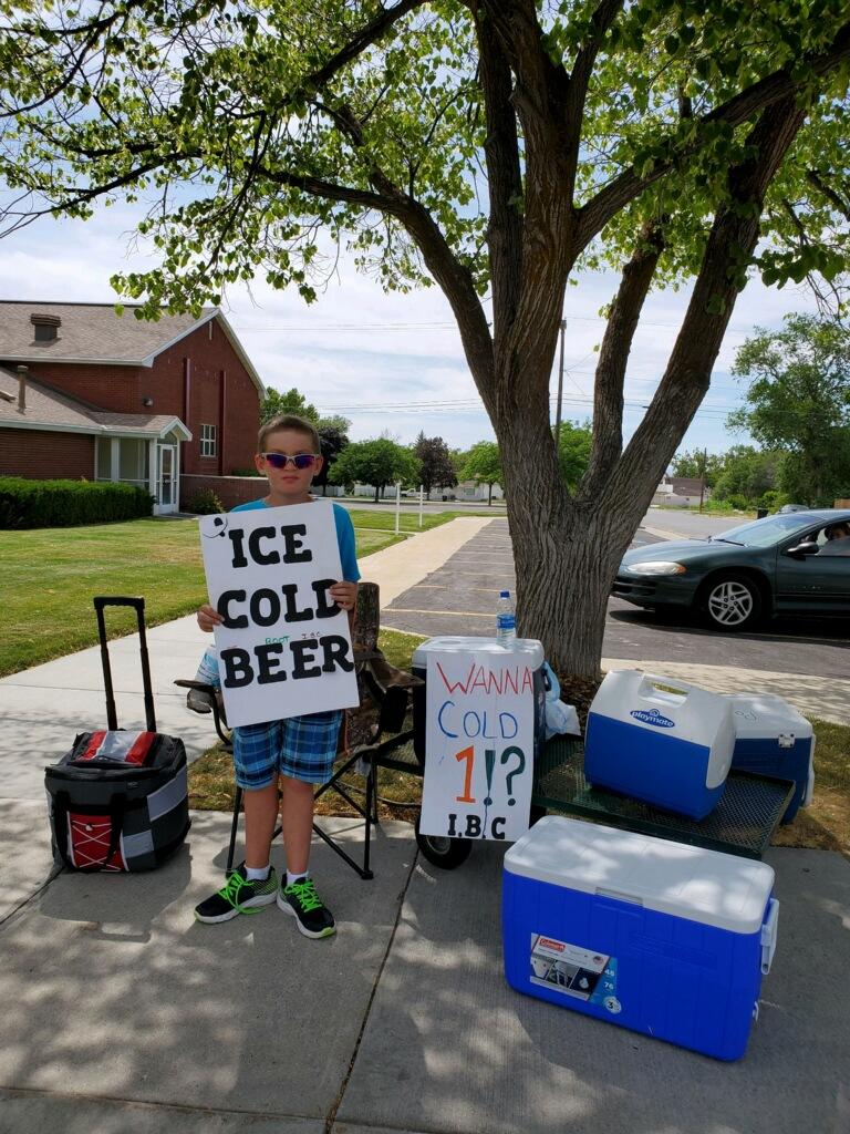 Seth poses with his bold signs at his root beer stand in Brigham City, Utah. (Credit: Alexis)
