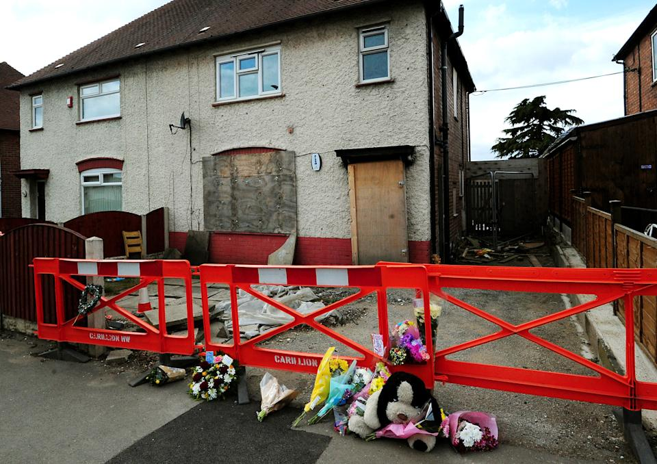 <p>Tributes were laid outside the home in which the children died</p>PA