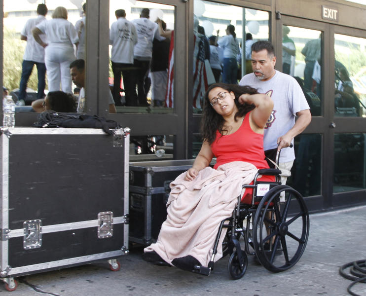 """CORRECTS TO AUG. 10, NOT 8 - Jessica Coca Garcia is wheeled away after speaking at League of United Latin American Citizens' """"March For a United America,"""" in El Paso, Texas, on Saturday, Aug. 10, 2019, a week after she and her husband were injured by bullets during a mass shooting. More than 100 people marched through the Texas border denouncing racism and calling for stronger gun laws one week after several people were killed in a mass shooting that authorities say was carried out by a man targeting Mexicans.  (AP Photo/Cedar Attanasio)"""