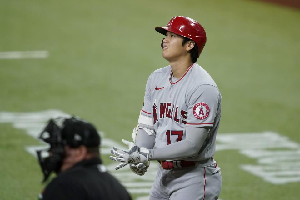 Umpire Sam Holbrook stands by the plate as Los Angeles Angels' Shohei Ohtani adjust his gloves during an at-bat in the first inning of a baseball game in Arlington, Texas, Tuesday, Sept. 28, 2021. (AP Photo/Tony Gutierrez)