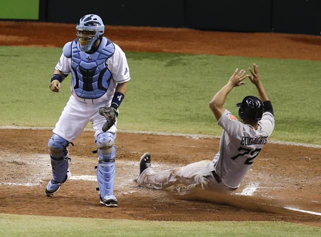 Tampa Bay Rays catcher Jose Molina, left, waits for a throw as Boston Red Sox's Xander Bogaerts (72) slides home to score a run in the ninth inning of Game 4 of baseball's American League division series, Tuesday, Oct. 8, 2013, in St. Petersburg, Fla. Boston won the game 3-1.(AP Photo/John Raoux)