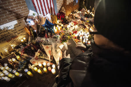 A woman recites from a Bible while standing over a makeshift memorial during a prayer vigil at the site where two New York Police Department (NYPD) officers were fatally shot in Brooklyn, New York December 21, 2014. REUTERS/Stephanie Keith