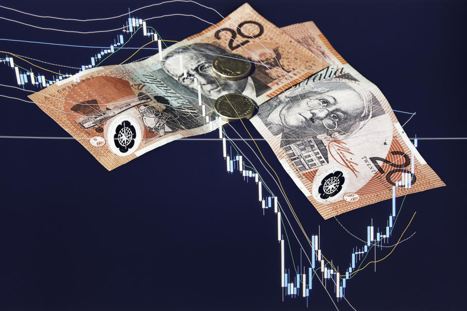 The financial market is having great impact over the markets around the world and the Australian Dollar. In this picture there is a chart of the stock market breakdown and two AUD banknotes and coins, due to the recession caused by Covid-19 flu