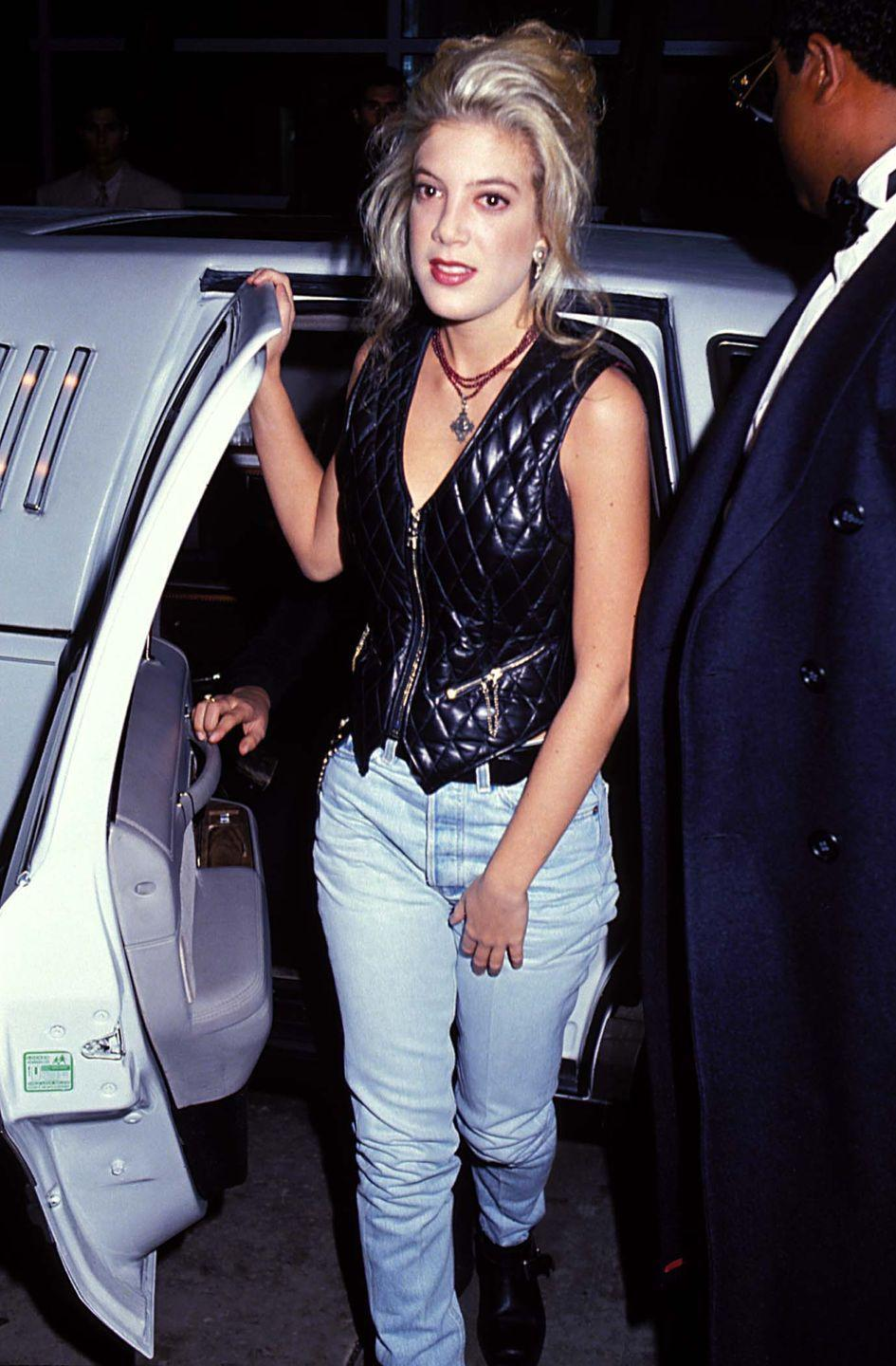 """<p>In 1991, the <em><a href=""""http://www.nytimes.com/1991/02/03/business/all-about-denim-the-appeal-of-blue-now-red-or-green-jeans.html"""" rel=""""nofollow noopener"""" target=""""_blank"""" data-ylk=""""slk:Times"""" class=""""link rapid-noclick-resp"""">Times</a></em> declared that """"sales of blue jeans...have been flagging,"""" but clearly they were still popular with Hollywood actresses like Tori Spelling , who wears an ultra-faded wash with her leather vest.</p>"""