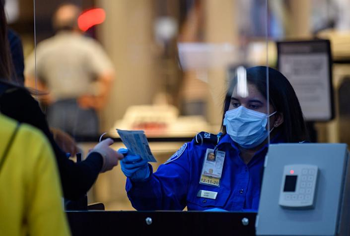 """<span class=""""caption"""">A passenger at Pittsburgh International Airport travels through security on May 7, 2020.</span> <span class=""""attribution""""><a class=""""link rapid-noclick-resp"""" href=""""https://www.gettyimages.com/detail/news-photo/travelers-make-their-way-through-ticketing-and-tsa-news-photo/1212133737?adppopup=true"""" rel=""""nofollow noopener"""" target=""""_blank"""" data-ylk=""""slk:Jeff Swensen/Getty Images"""">Jeff Swensen/Getty Images</a></span>"""