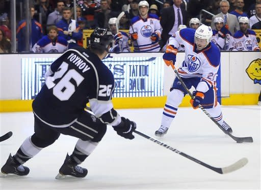 Edmonton Oilers' Eric Belanger right, shoots as Los Angeles Kings' Slava Voynov defends during the second period of an NHL hockey game, Monday, April 2, 2012, in Los Angeles. (AP Photo/Richard Hartog)