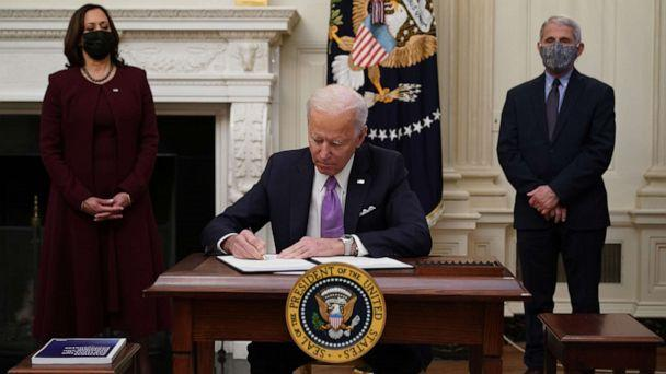 PHOTO: President Joe Biden signs executive orders as part of the COVID-19 response as Vice President Kamala Harris and Director of NIAID Anthony Fauci look on in the State Dining Room of the White House in Washington, D.C., Jan. 21, 2021. (Mandel Ngan/AFP via Getty Images)