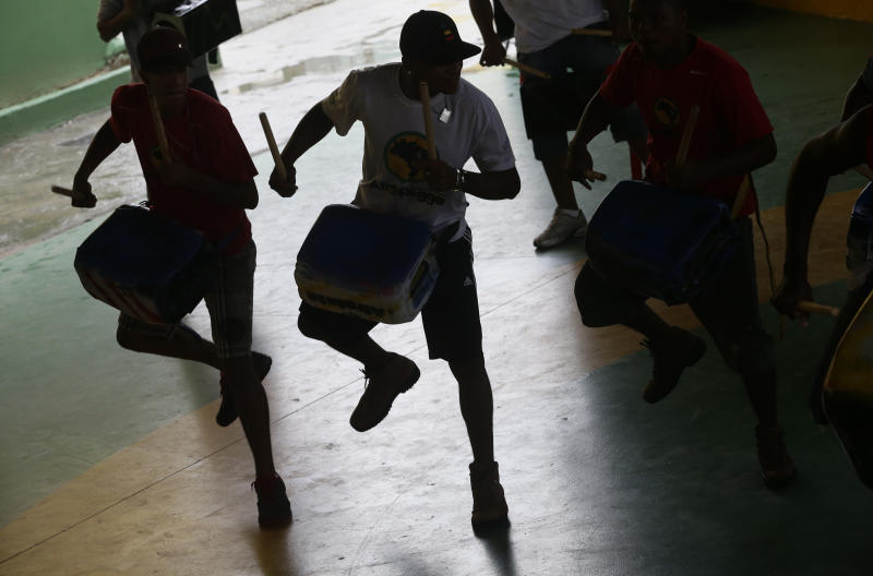 Musicians from Afro Reggae play drums during a presentation for London's Royal Opera House members in the Vigario Geral slum in Rio de Janeiro, Brazil, Saturday, March 2, 2013. This past week Royal Ballet dancers shared their knowledge and advice with promising artists during an education symposium between the company and the cultural arts center Afro Reggae. (AP Photo/Silvia Izquierdo)