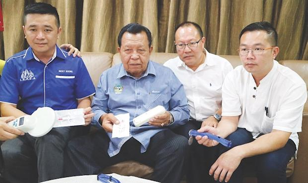 Ipoh Society for Prevention of Cruelty to Animals president Ricky Soong (left) showing the microchips that will be inserted into stray dogs that have been neutered or spayed. — Picture by Malay Mail