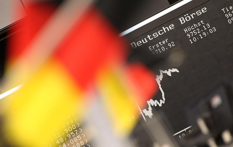 German flags are pictured in front of a display showing the German DAX stock market index at the stock exchange in Frankfurt, Germany, on July 14, 2014
